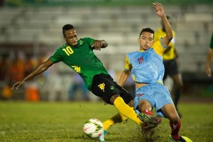 Junior Flemmings tackles St Lucian player - Image via jamaicafootballfederation.com